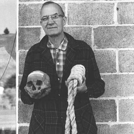 Howard A. Black, Grant County Museum curator, with skull of Berry Way and hangman's rope.